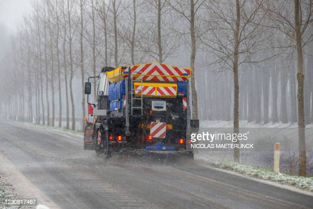 Illustration shows a salt spreading truck driving through a snowy winter landscape in Damme, in Flanders, Saturday 16 January 2021. BELGA PHOTO...