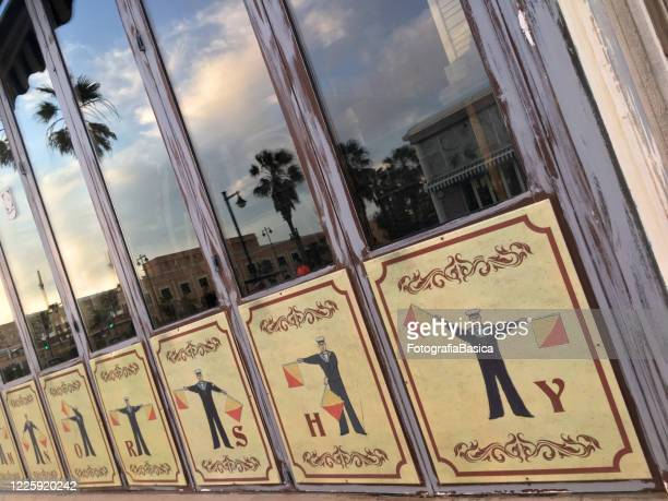 illustrations of sailor demonstrating flag semaphore system - semaphore stock pictures, royalty-free photos & images