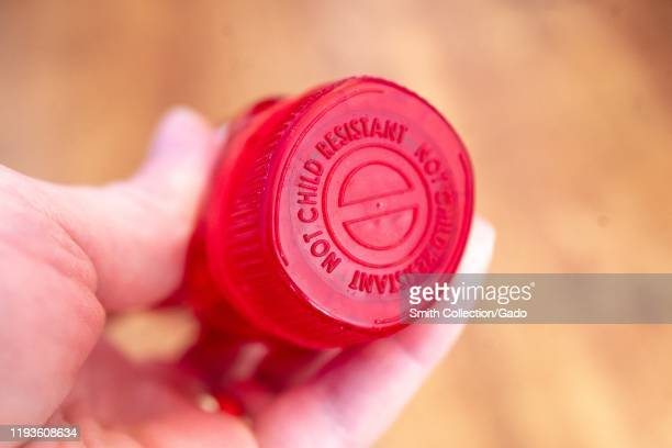 Illustrative image closeup of hand of a man against a light wooden background holding a bottle of the combination narcotic opioid pain medication...