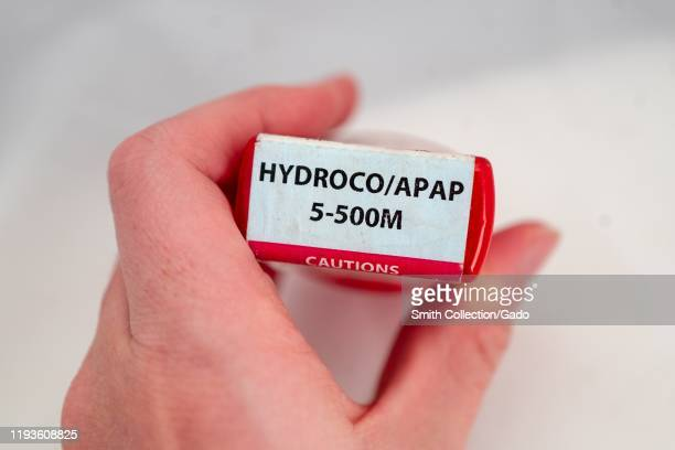 Illustrative image closeup of hand of a man against a white background holding a bottle of the combination narcotic opioid pain medication...