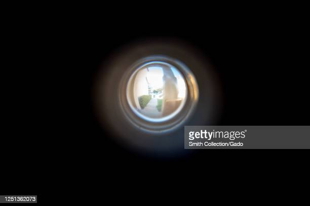 Illustrative image looking out the door peephole in front door of suburban home in San Ramon, California, suggesting security or theft, June 18, 2020.