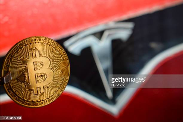 Illustrative image of a commemorative bitcoin in front of the Tesla car logo. Tesla, led by Elon Musk, confirmed that it purchased about $ 1.5...