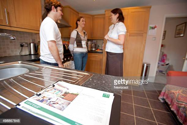 Illustrative image of a young couple being shown around a house by an Estate Agent.