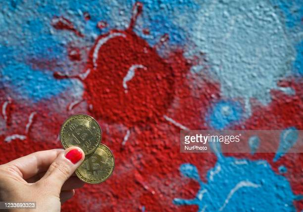 Illustrative image of two commemorative bitcoins seen in front of a mural representing the coronavirus molecules. On Sunday, 27 June 2021, in Dublin,...