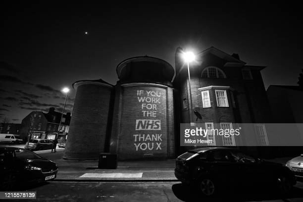 Illustrator and artist Mike Dicks projects messages onto a wall of a church on March 29, 2020 in Brighton & Hove, England . Coronavirus pandemic has...