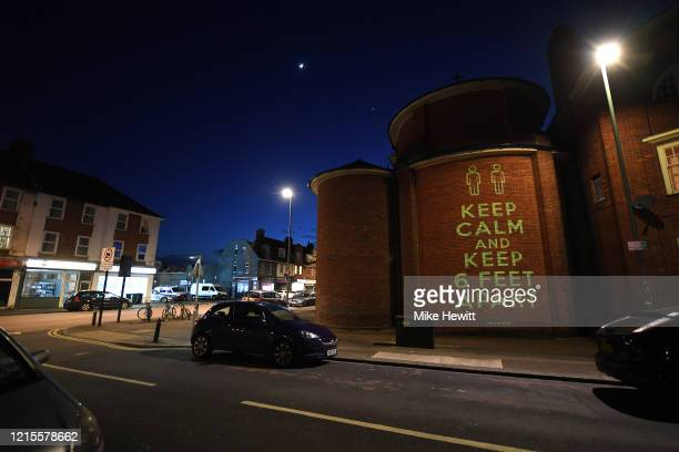 Illustrator and artist Mike Dicks projects messages relating to government advice during the coronavirus outbreak onto the wall of a church on March...