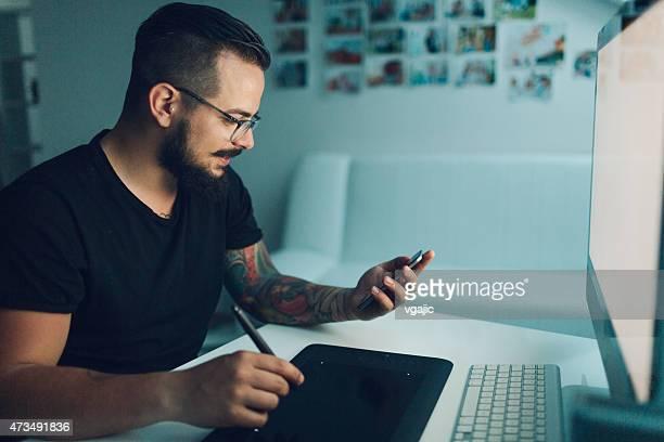Ilustrador trabajo escribiendo en su smartphone.