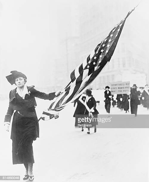 Illustrator Neysa McMein carries a large American flag in a parade championing the right of women to vote