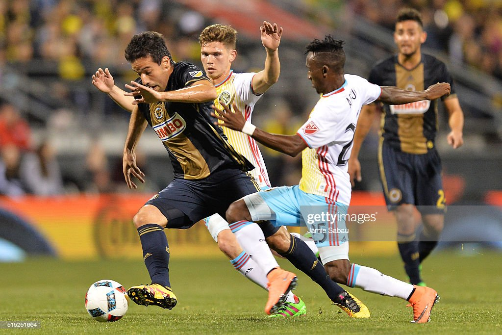 Ilsinho #25 of the Philadelphia Union moves the ball upfield as Will Trapp #20 of the Columbus Crew SC and Harrison Afful #25 of the Columbus Crew SC defend in the first half on March 12, 2016 at MAPFRE Stadium in Columbus, Ohio.