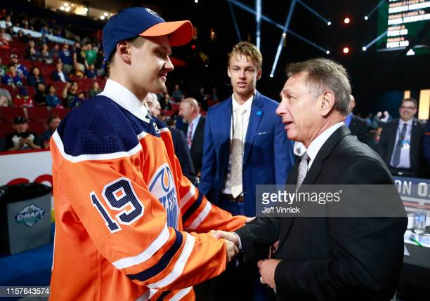 Ilya Konovalov 85th overall pick of the Edmonton Oilers is greeted by general manager Ken Holland on the draft floor during Rounds 27 of the 2019 NHL...
