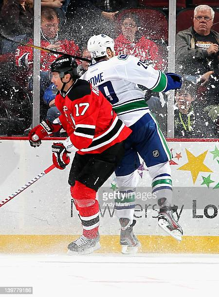 Ilya Kovalchuk of the New Jersey Devils and Aaron Rome of the Vancouver Canucks collide near the boards during the game at the Prudential Center on...