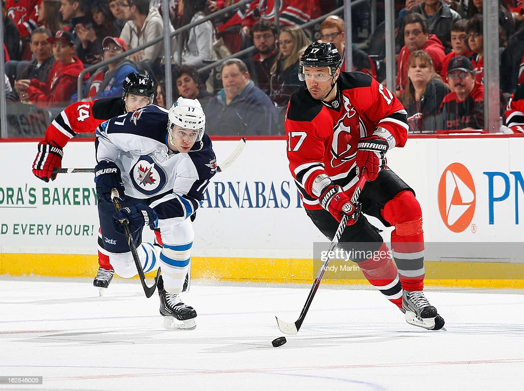Ilya Kovalchuk #17 of the New Jersey Devils plays the puck while being pursued by James Wright #17 of the Winnipeg Jets during the game at the Prudential Center on February 24, 2013 in Newark, New Jersey.