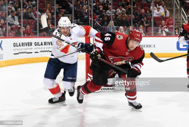 Ilya Lyubushkin of the Arizona Coyotes battles for a loose puck with Mark Pysyk of the Florida Panthers at Gila River Arena on February 25 2020 in...