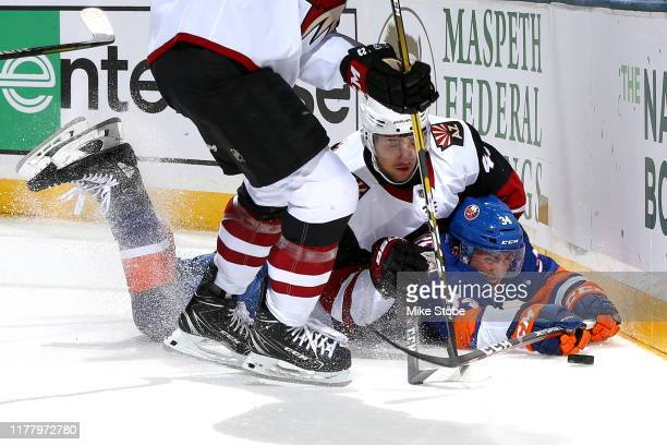 Ilya Lyubushkin of the Arizona Coyotes battles for the puck with Cole Bardreau of the New York Islanders during the first period at NYCB Live's...