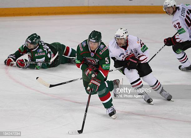Ilya Nikulin of the Ak Bars and Alexander Frolov of the Avangard scrambles to keep control of the puck during the game between Avangard and Ak Bars...