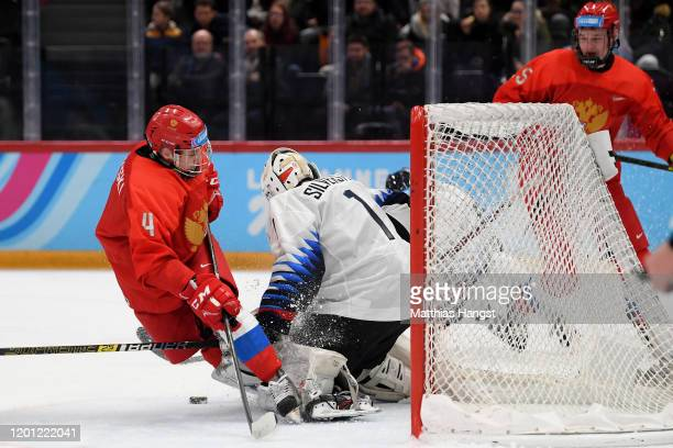 Ilya Rogovski of Russia and Dylan Silverstein of USA battle for the puck during the Men's 6Team Ice Hockey Tournament Finals Gold Medal Game between...