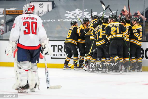 Ilya Samsonov of the Washington Capitals looks on as Craig Smith of the Boston Bruins reacts with teammates after scoring the game-winning goal in...