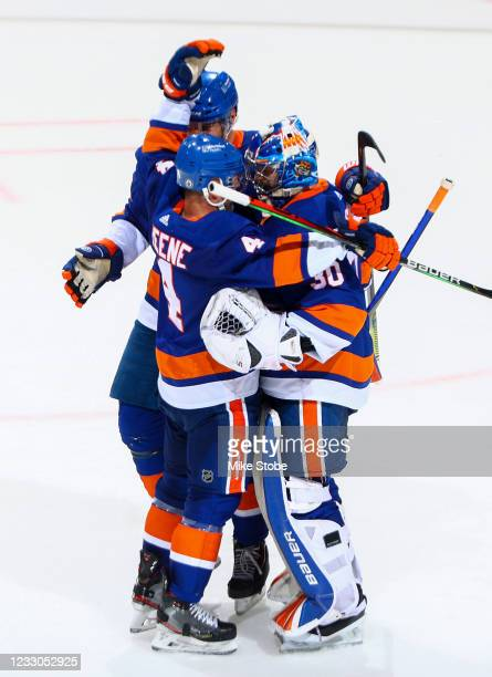 Ilya Sorokin and Andy Greene of the New York Islanders celebrate after their teams 4-1 victory against the Pittsburgh Penguins in Game Four of the...