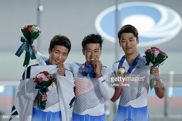 Im Chaebin Kang Dongjin and Son Jeyong of South Korea celebrate with their gold medals after the Cycling Track Men's Team Sprint Final during the...