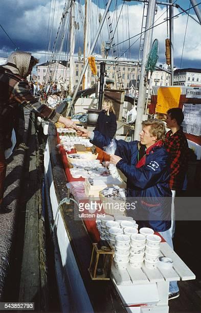 Im Hafen von Helsinki kann man Fischspezialitäten direkt vom Kutter kaufen Die Verkäufer haben ihre Ware auf Holzbänken ausgelegt die als...