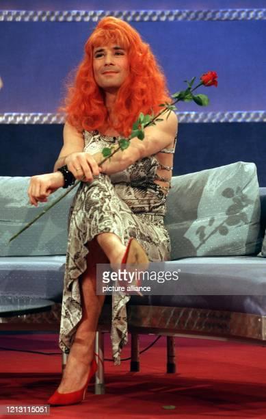 """Im hochgeschlitzten Kroko-Kleid mit roten Pumps und roten Haaren sitzt Wett-Gast Kai Pflaume bei """"Wetten, dass ...?"""" am 26.2.2000 in Köln auf der..."""