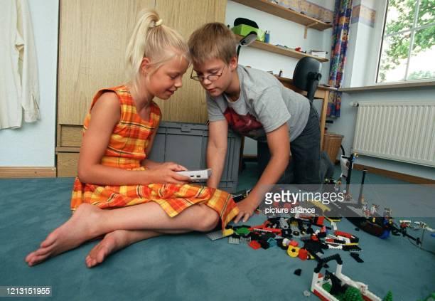Im Kinderzimmer spielt die neunjährige Judith mit einem Gameboy, ihr zwei Jahre älterer Bruder Simon schaut dabei zu.