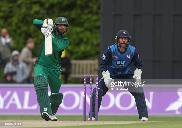 Imad Wasim of Pakistan bats on his way to a century as Kent's Adam Rouse looks on during the tour match between Kent and Pakistan at the County...