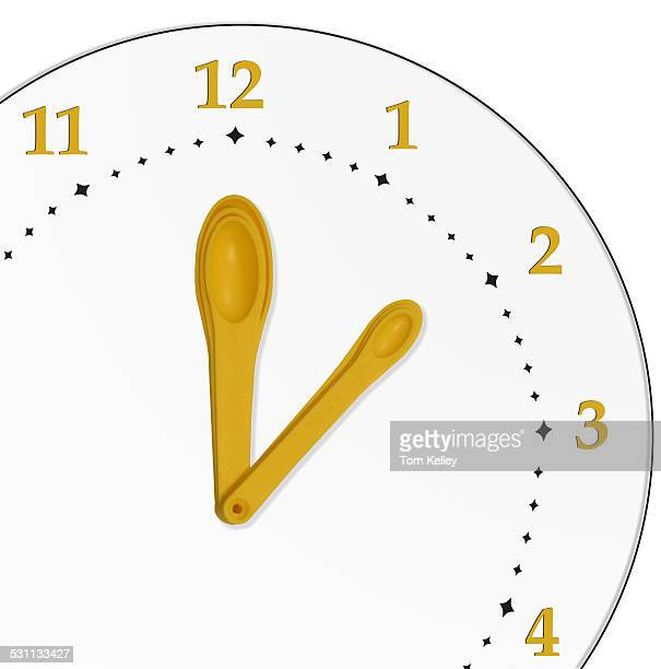 Image composite features a white, clock face with a set of yellow measuring spoons that act as hands, 2013.
