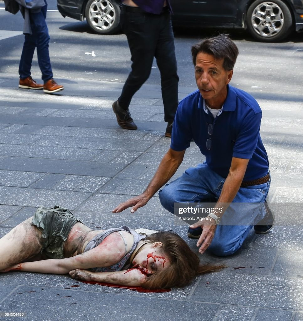 Image contains graphic content.] A victim woman lays on the ground a maroon sedan vehicle plowed into pedestrians on a busy sidewalk on the corner of West 45th St. and Broadway at Times Square, New York, NY United States on May 18, 2017. Multiple pedestrians were struck Thursday by a speeding vehicle in the heart of New York City, according to reports. At least 13 people wounded.