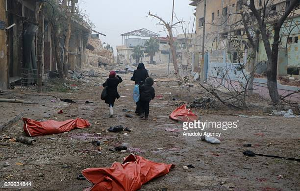 Image depicts death] A teenage girl and two kids run among the dead bodies on the ground at the site of blast after Assad Regime's strike over...