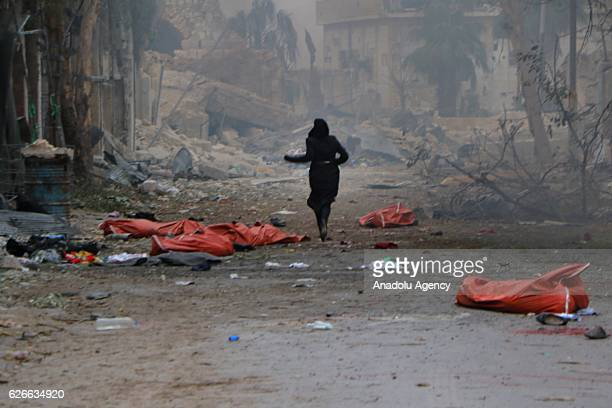 Image depicts death] A teenage girl runs among the dead bodies on the ground at the site of blast after Assad Regime's strike over civilians in...