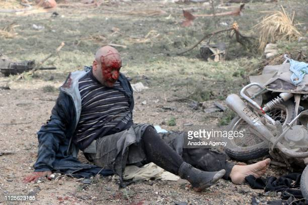 Image depicts graphic content] A wounded man lays on the ground around the site after the consecutive bomb attacks with two bombladen vehicles in...