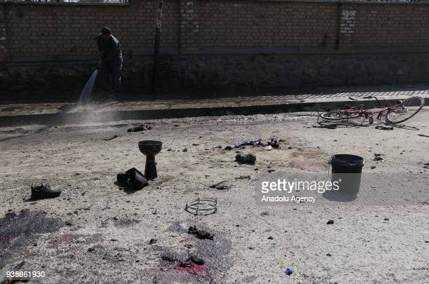 Image depicts graphic content] An Afghan official cleans the explosion site after a suicide bomb blast that targeted a shrine visited by Shi'ite...