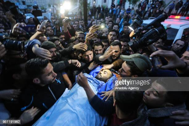Image depicts graphic content] Palestinian mourners carry the body of Palestinian journalist Ahmed Abu Hussein at a hospital in Beit Lahia, in the...
