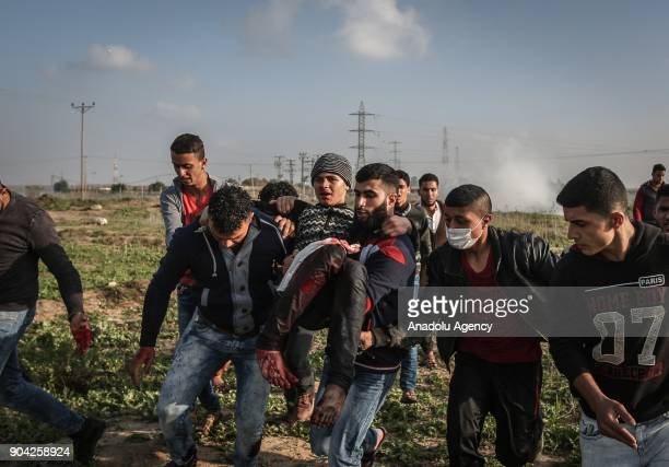 Image depicts graphic content] Palestinians carry a wounded protester after Israeli security forces' intervention during a protest against US...