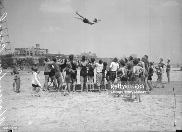 Image of a boy flying in midair above a crowd of people who are holding a large blanket standing on the sand at Clarendon Beach in the Uptown...