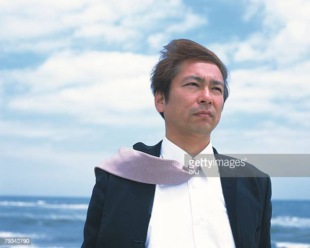 Image of a Businessman Standing at the Beach Under a Blue Sky, the Wind Blowing, Low Angle View