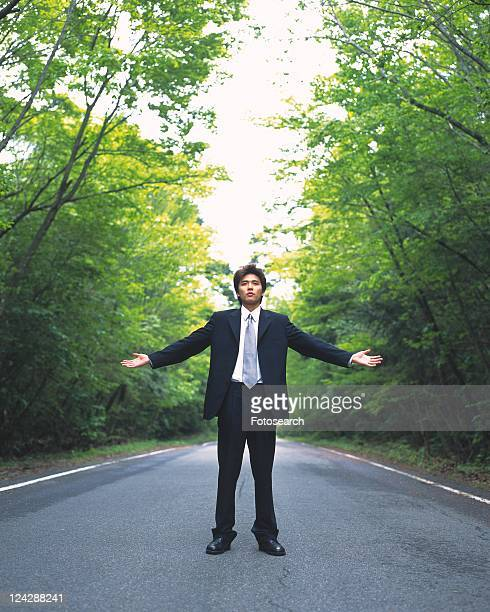 Image of a Businessman Standing in the Street with his Arms wide Open, Surrounded By Trees, Front View, Looking at Camera