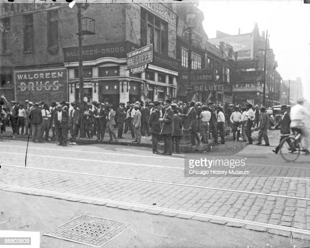 Image of a crowd of African American men standing on the sidewalks in front of a Walgreen Drugs at 3501 South State Street at the corner of 35th and...