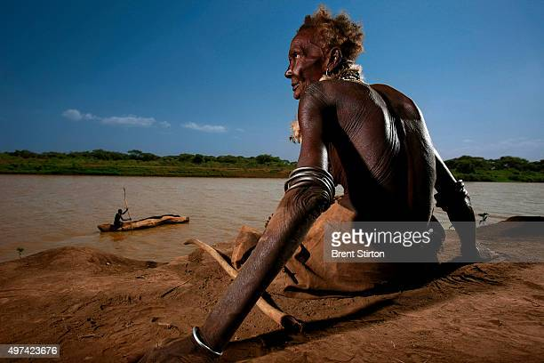Image of a Dassanech elderly woman sitting on the banks of the all important Omo River the chief life source in the Lower Omo Valley South West...