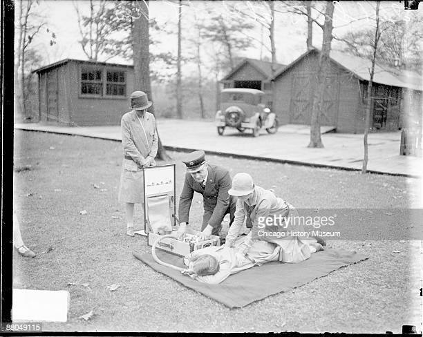 Image of a Girl Scout kneeling over a girl lying prone during First Aid practice at Great Lakes Naval Training Station in Illinois 1928 A man wearing...