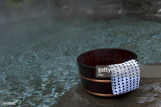 image of a japanese outdoor hot spring bath, tub and tenugui at the side, close up - 手ぬぐい ストックフォトと画像
