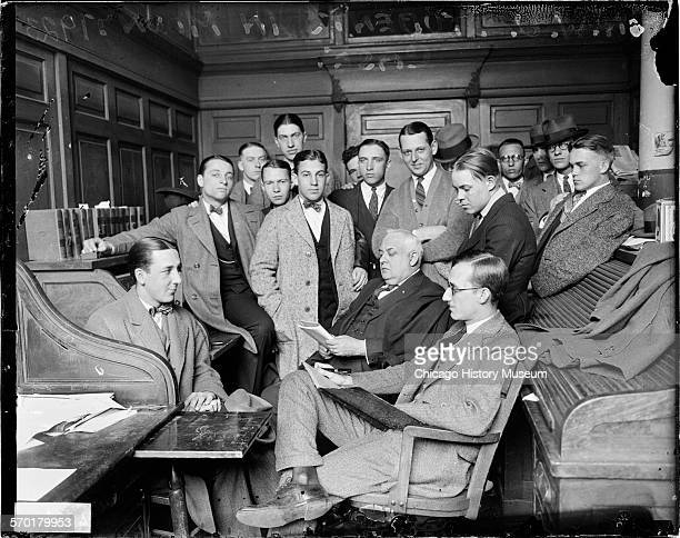 Image of a large group of Northwestern University students associated with the hazing murder case of Leighton Mount standing behind three men sitting...