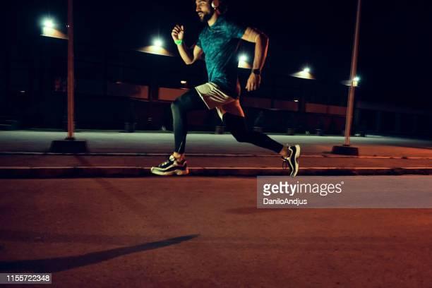 afbeelding van een man sprinten in de straat 's nachts - baanevenement mannen stockfoto's en -beelden