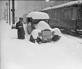 Image of a man standing in knee deep snow next to a parked halfburied picture id89730553?s=170x170