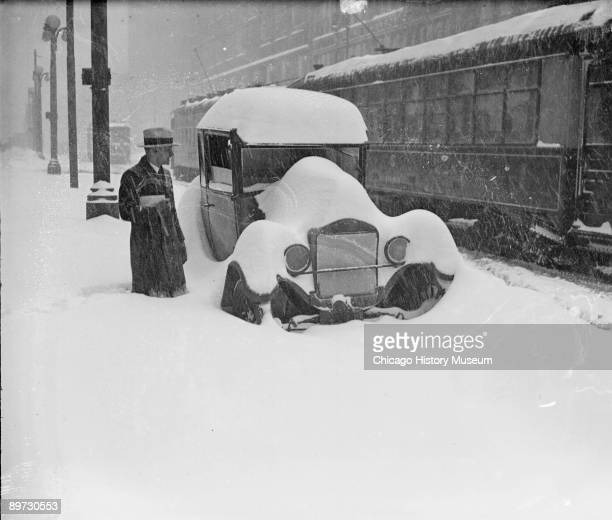 Image of a man standing in knee deep snow next to a parked halfburied automobile with snow piled on the roof hood and around the wheels on a street...
