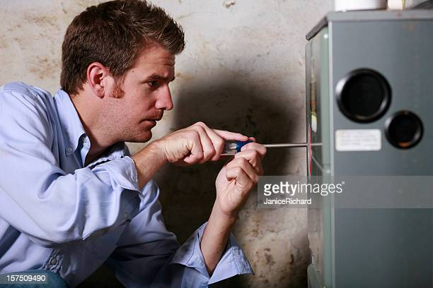 Image of a man working on a furnace with a screwdriver