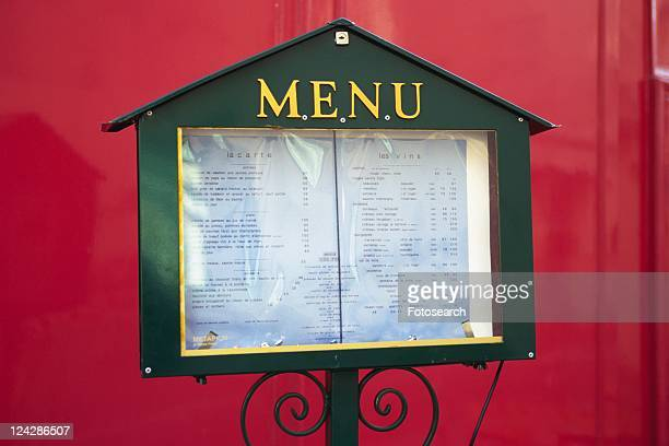 Image of a Menu of a Restaurant in a Little Box In Front of a Red Wall, Front View, Paris, France