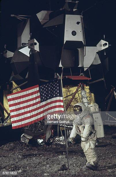 Image of a museum exhibit that shows an astronaut as he stands next to an American flag on the surface of the moon 1970s