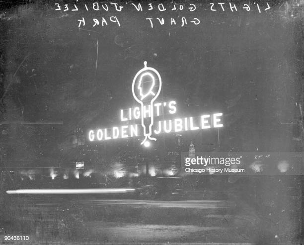 Image of a neon sign for Light's Golden Jubilee sitting in Grant Park viewed at night celebrating the 50th anniversary of Thomas Edison's...